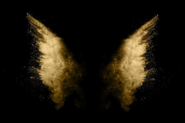 Golden powder explosion on black background. Premium Photo