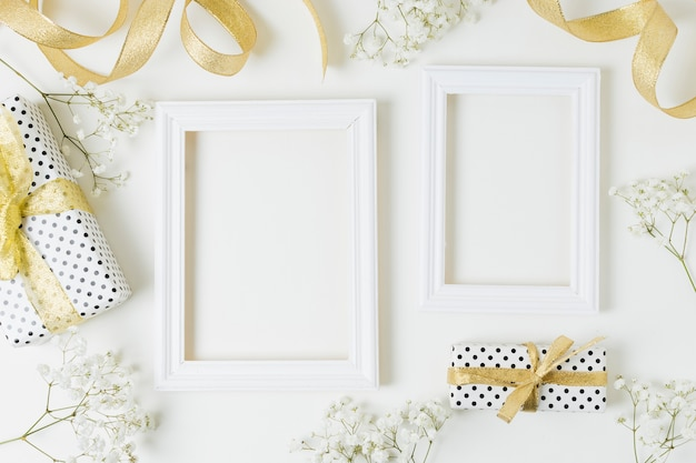 Golden ribbon; gift boxes; baby's-breath flowers near the wooden frame on white backdrop Free Photo