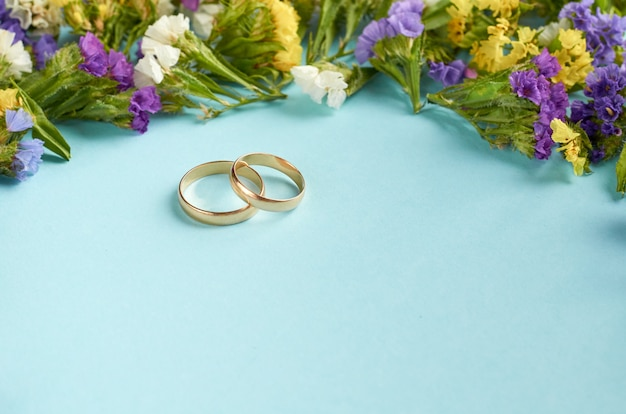 Golden rings with colored flowers on blue surface, wedding template. Premium Photo
