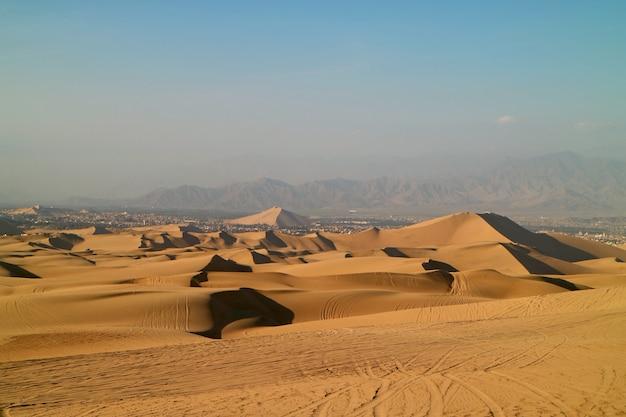 Golden sand dunes with the wheel prints of dune buggies, huacachina, ica, peru Premium Photo