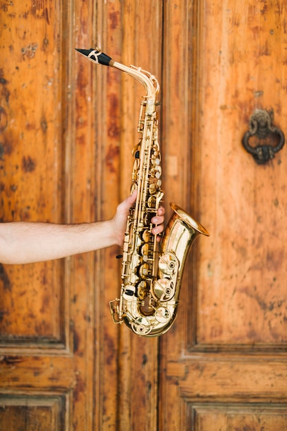 Golden saxophone with wooden background Free Photo