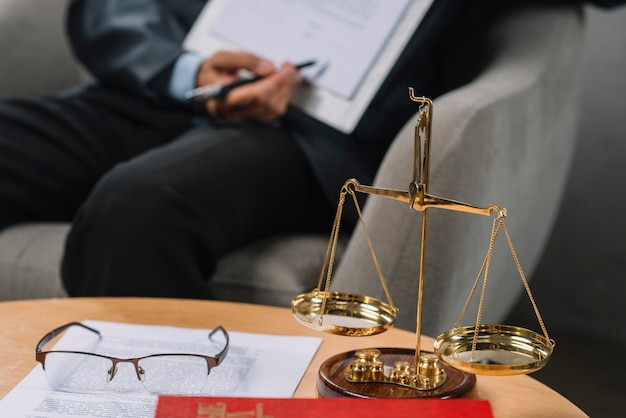 Golden scale justice in front of lawyer pointing on contract in the court room Free Photo