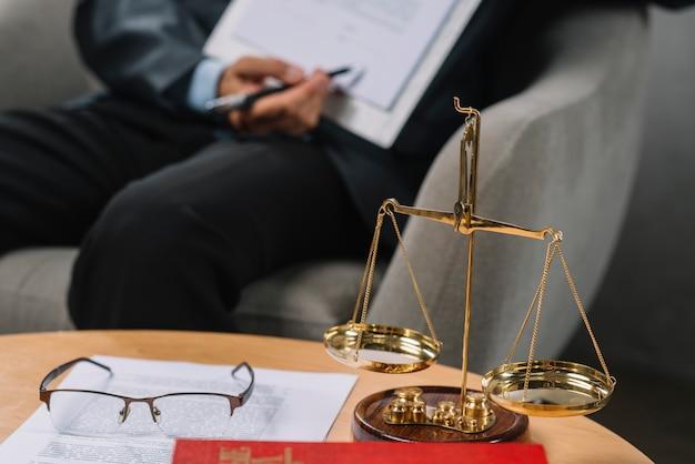 Золотая шкала правосудия перед адвокатом, указывающим на контракт в зале суда Premium Фотографии