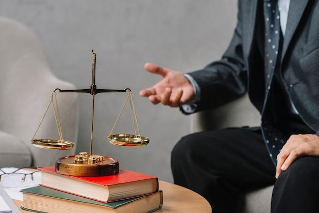Золотая шкала на стеке книги перед мужской юрист, сидя на стуле, жесты Premium Фотографии