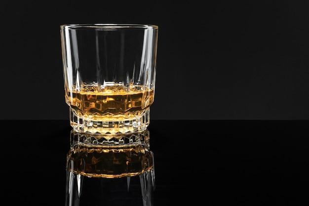Whisky scozzese dorato su fondo nero Foto Gratuite