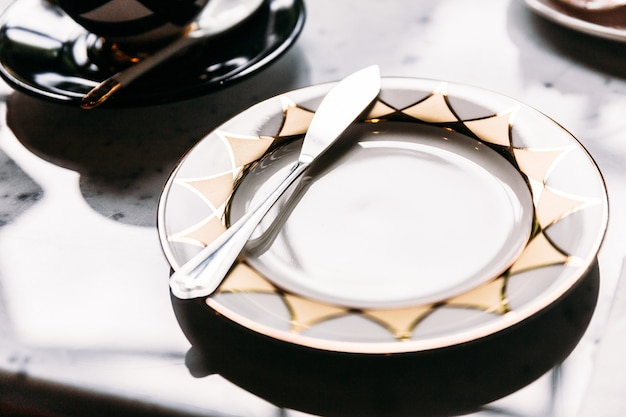 Golden and silver pattern shiny empty plate with butter knife on marble top table. Premium Photo