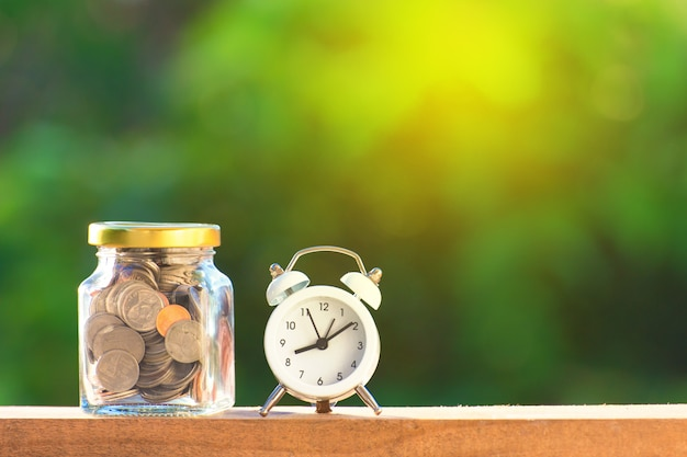 Golden and silver with closed bottle coin with white alarm clock on beautiful natural green background. Premium Photo