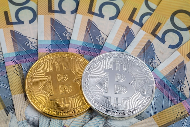 Golden and sliver bitcoins on pile of australian 50 dollar banknotes closeup Premium Photo