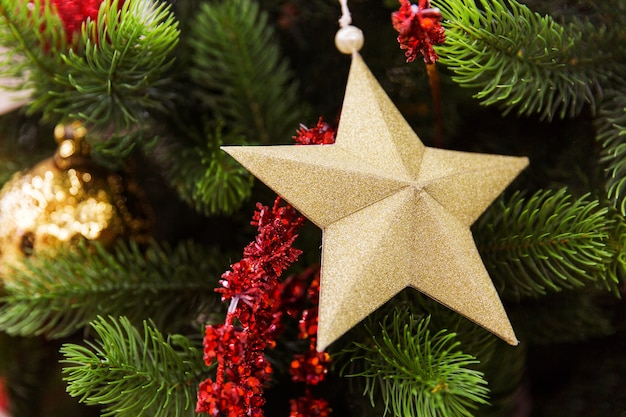 クリスマスツリーブランチに黄金の星。新年のおもちゃ。新年の準備 Premium写真