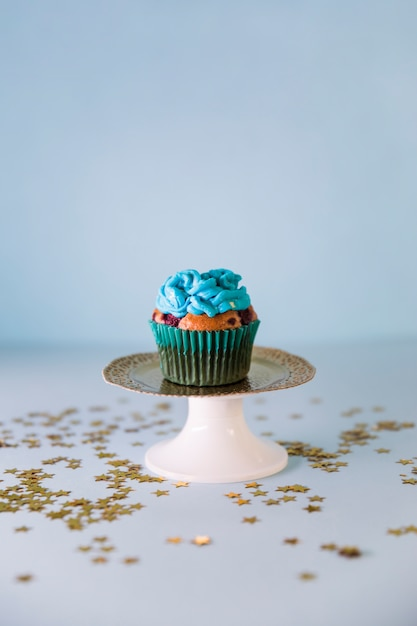 Golden stars spread over the fresh tasty birthday cupcake on cakestand on blue backdrop Free Photo
