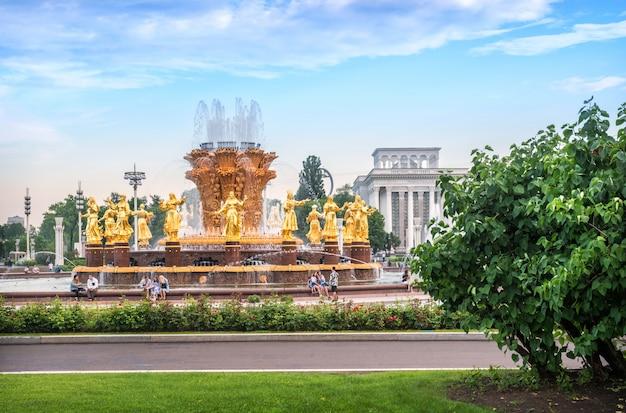 夏の緑の中でモスクワのvdnhで噴水の友情の黄金の像。キャプション:robostation Premium写真