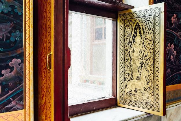 Golden thai angel decorated on window inside thai monastery at bodh gaya, bihar, india. Premium Photo
