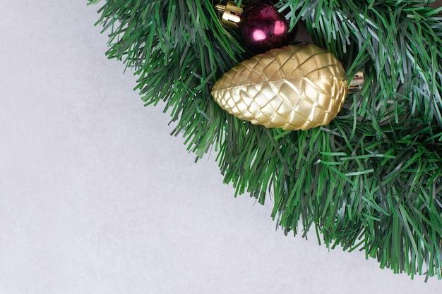 흰색 표면에 녹색 반짝이에 Pinecone의 황금 장난감 무료 사진