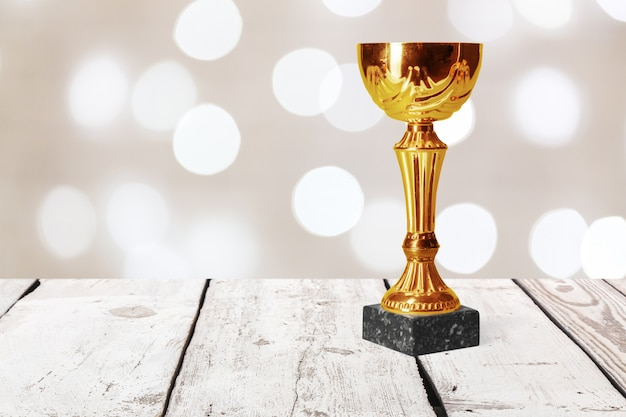 Golden trophy on wood table Premium Photo
