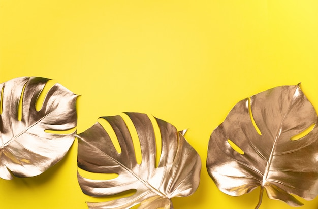 Golden tropical monstera leaf on yellow background with copy space. Premium Photo