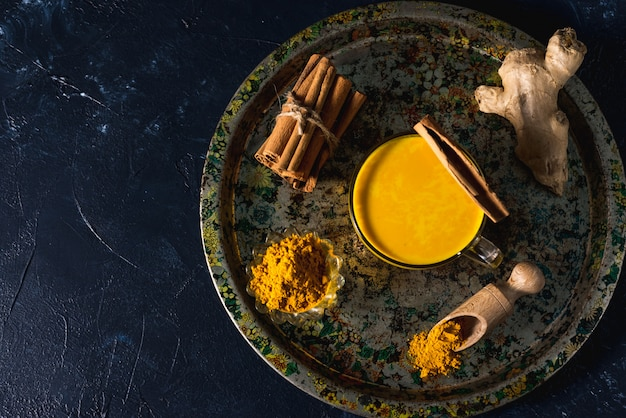 Golden turmeric milk on the dark surface with spices cinnamon and ingredients Premium Photo