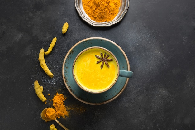 Golden turmeric milk with curcuma powder and anise star on black. view from above. Premium Photo