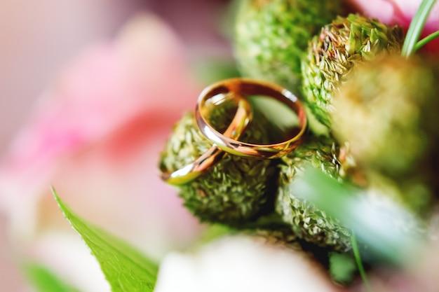 Golden wedding rings on brunia flower Premium Photo
