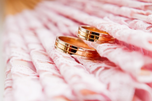 Golden wedding rings on lace pink fabric. wedding embroidery detail. Premium Photo
