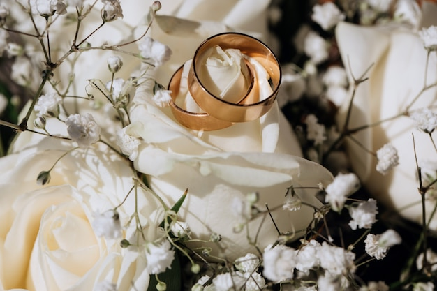 Golden wedding rings on the white rose  from the wedding bouquet Free Photo