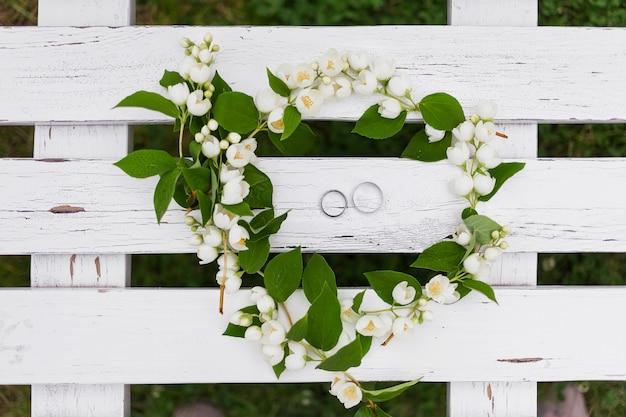 Golden wedding rings with diamonds lie inside jasmine flower in bridal bouquet Premium Photo