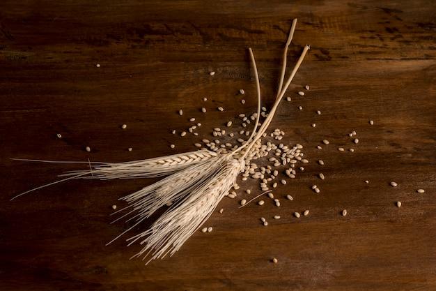 Golden wheat spikes on wood Free Photo