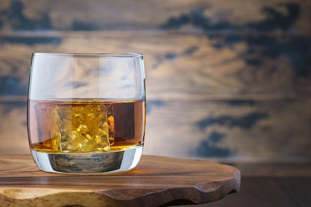 Золотой виски или бурбон с кубиками льда в стакане. на деревянном столе стакан с виски или бренди. алкогольный напиток Premium Фотографии