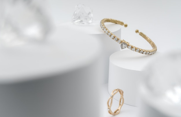 Golden with diamonds bracelet between diamonds on white platform Premium Photo