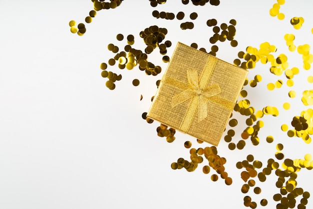 Golden wrapped gift surrounded by confetti Free Photo
