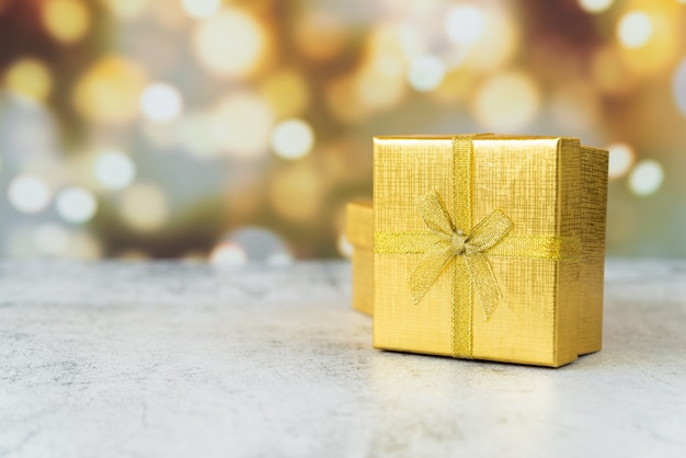 Golden wrapped gift with bokeh effect Free Photo