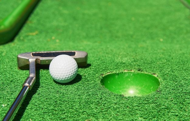 Golf ball and golf club on artificial grass. Free Photo