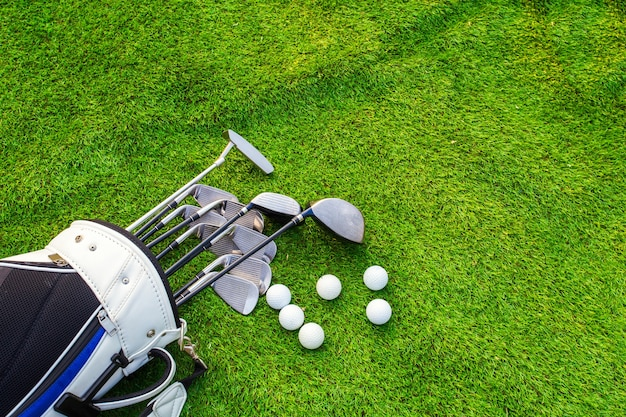 Golf ball and golf club in bag on green grass Premium Photo