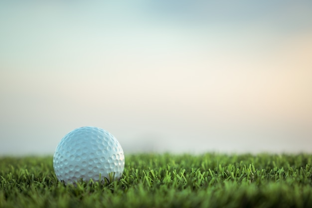 Golf ball on grass on sky background Premium Photo