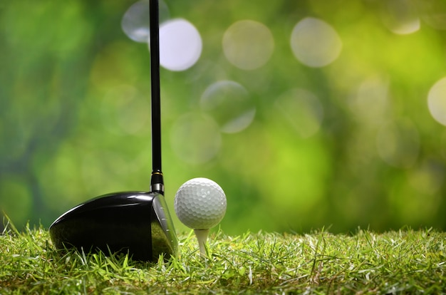 Golf ball on green grass ready to be struck on golf course background Premium Photo