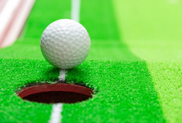 Golf ball on lip of cup, goal concept Premium Photo