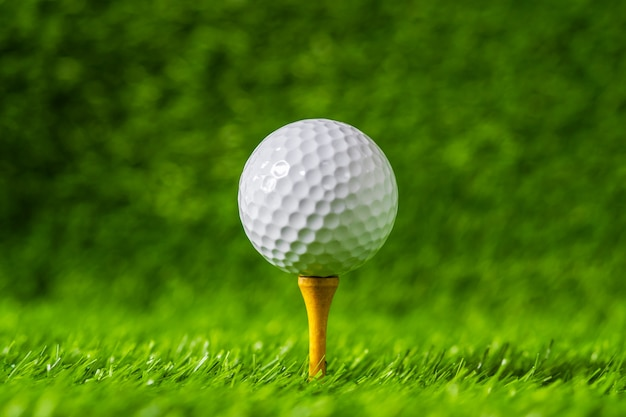 Golf Ball With Green Grass Background On Tee Closeup Premium Photo