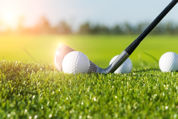 Golf club and ball in grass and sunset Premium Photo