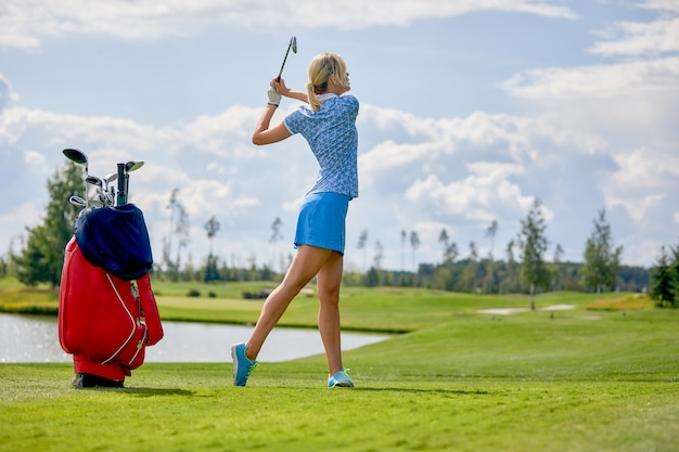 Golf course, a beautiful girl getting ready to hit the ball. lifestyle concept, golf concept, pursuit of excellence, craftsmanship, royal sport. Premium Photo