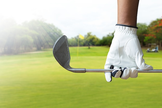 Golf player holding a golf club in golf course Premium Photo