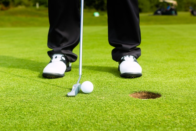 Golf player putting ball in hole Premium Photo