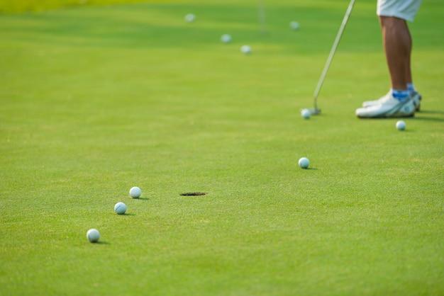 Golf player putting golf ball Premium Photo