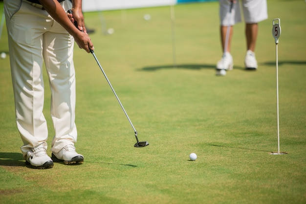 Golf player at the putting green hitting ball into a hole Premium Photo