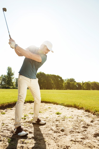 Golfer about to hit ball out of a sand bunker Free Photo
