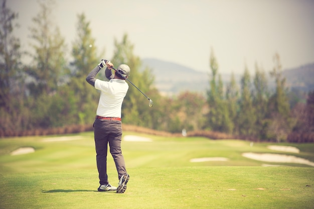 Golfers hit sweeping golf course in the summer vintage color Premium Photo
