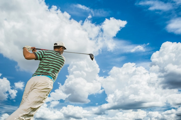 Golfers will tee hit the golf ball with the force on a clear day Premium Photo