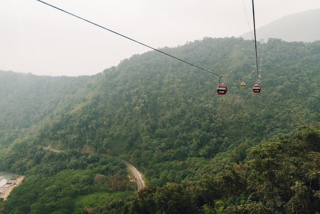 Gondola lifts moving over mountain with green trees in the area of sun moon lake ropeway in yuchi township, nantou county, taiwan. Premium Photo