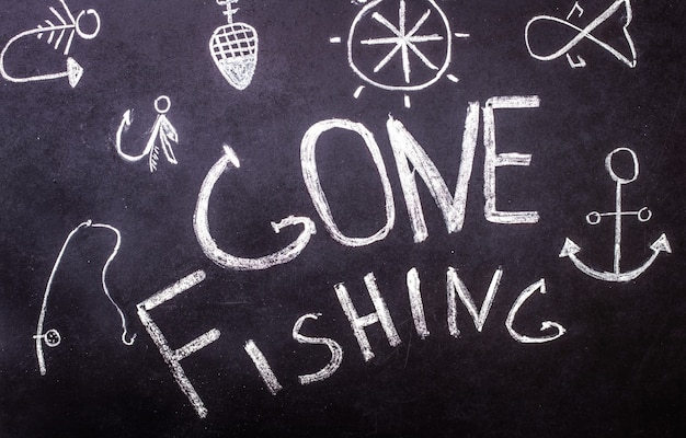 Gone fishing chalk inscription on chalkboard with marine drawings Free Photo