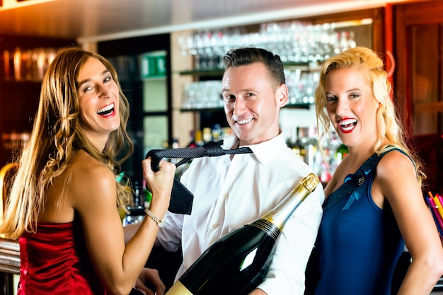 Good friends, bartender and women - with a large magnum bottle champagne at bar having fun, she pulls on his tie Premium Photo