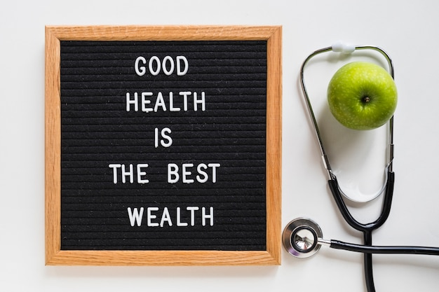 Good health message board with green apple and stethoscope on white background Free Photo