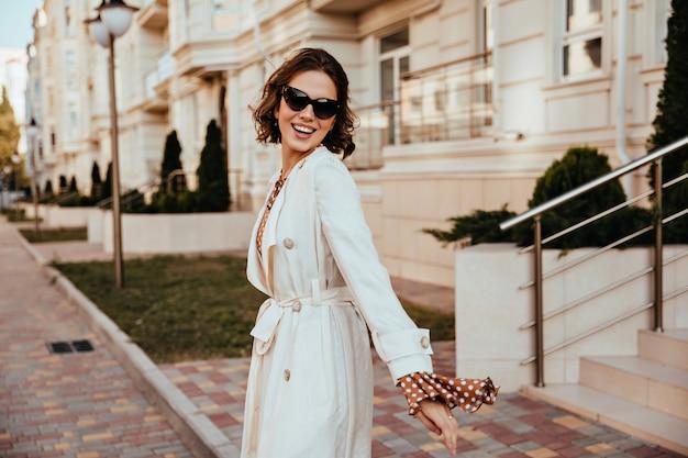 通りで笑っている長いコートを着た気さくな女の子。街で時間を過ごす身なりのよいヨーロッパの女性。 無料写真